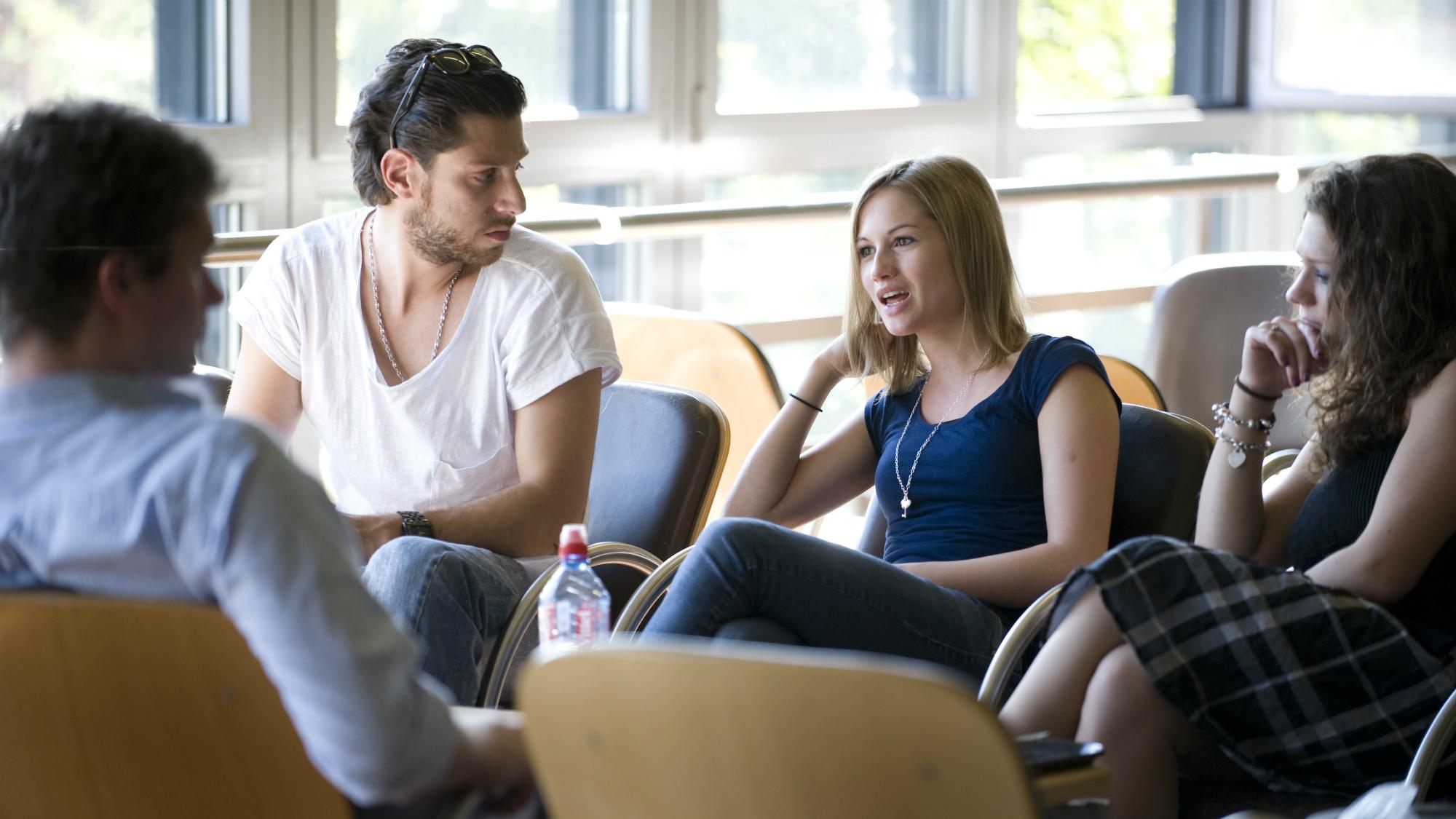 Studierende sitzen in den Stühlen vor dem Audimax an der Universitaet St.Gallen (HSG)